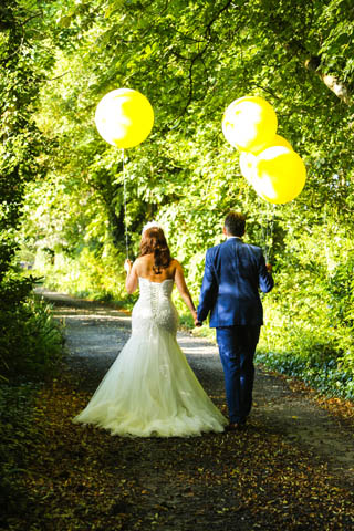 Bride and Groom walking with balloons.